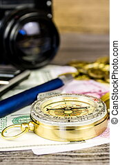 Composition of a tourist compass, banknotes, coins, calculator, pen