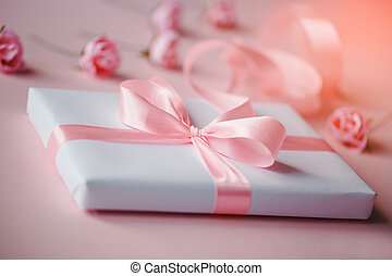 Composition of a white box and small pink flowers on a light pink background. Packing of gifts