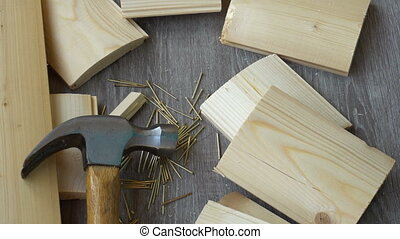 composition of boards, nails and hammer, hand hammer puts in the frame