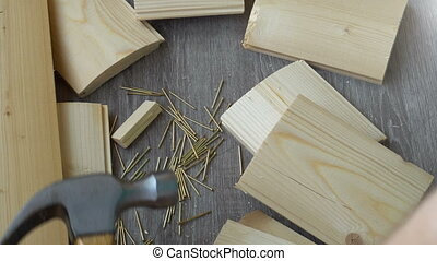 composition of boards, nails and hammer, the hand takes the hammer out of the frame