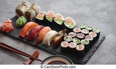 Composition of different kinds of sushi rolls placed on...