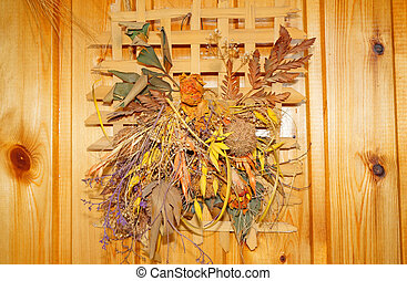 Composition of dried flowers and leaves on a wooden wall
