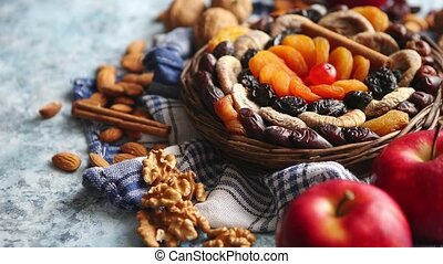 Composition of dried fruits and nuts in small wicker bowl...