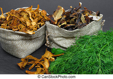 Composition of dry boletus and chanterelles mushrooms placed in canvas bags with dill and parsley broom on black stone background surface