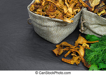 Composition of dry boletus and chanterelles mushrooms placed in canvas bags with dill and parsley broom on black stone background surface with copy space