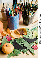 Composition of dry leaves, black paper bats, small pumpkin and other stuff