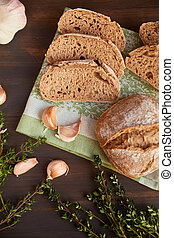 Composition of garlic and bread on a dark wooden table....