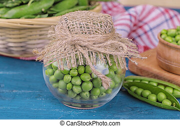 composition of green fresh peas in a jar on a blue wooden table close-up