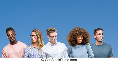 Composition of group of friends over blue blackground looking away to side with smile on face, natural expression. Laughing confident.