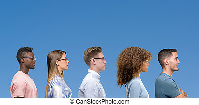 Composition of group of friends over blue blackground looking to side, relax profile pose with natural face with confident smile.