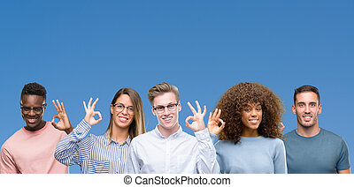 Composition of group of friends over blue blackground smiling positive doing ok sign with hand and fingers. Successful expression.