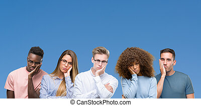 Composition of group of friends over blue blackground thinking looking tired and bored with depression problems with crossed arms.