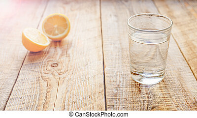 composition of halved lemon and glass with water wooden table