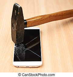 Composition of a hammer and a smart phone with a broken screen over the wooden surface