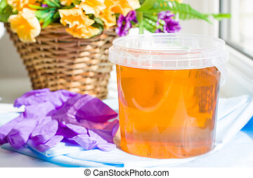 composition of jar sugar paste or wax honey for hair removing with purple gloves and flowers - depilation and beauty concept