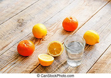 composition of lemons, oranges and glass with water wooden table