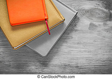 Composition of notebooks on wooden board office concept