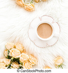 Composition of pastel tea rose bouquet flowers and a Cup of cocoa on white background. Floral background. Flat lay, top view.