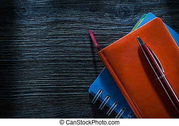 Composition of pocketbooks pen on vintage wooden board