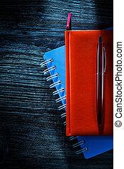 Composition of pocketbooks pen on wooden board
