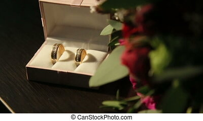 Composition of red box with golden shiny wedding rings and red roses on foreground