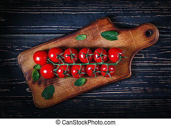 Composition of tomatoes on a wooden board