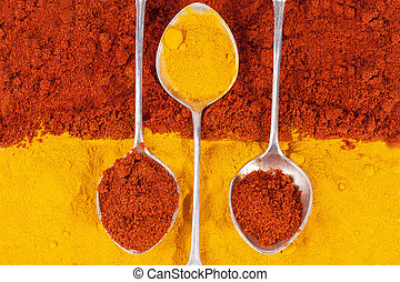 composition of turmeric and chili pepper powder with silver spoons
