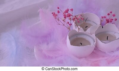 DIY. Do it yourself. Composition of White egg shell with burning candle inside. Bright easter decorations with bird feathers dry flowers. Pastel colors. Flame smoke