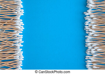 Composition of wooden cotton swabs on a blue-cyan-lilac background. Round frame framing. Flat lay. Copy space. Trend. The concept is natural, eco-friendly, modern hygiene..