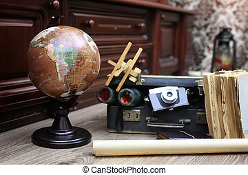 composition on a wooden floor vintage globe with old leather sui