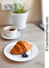 composition with a cup of coffee and a croissant on the table on the Place for the text