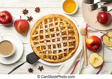 Composition with apple pie and ingredients on wooden background, top view