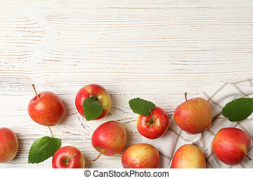 Composition with apples and towel on white wooden background, top view
