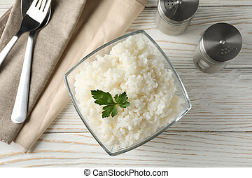 Composition with bowl of delicious rice on wooden background, top view