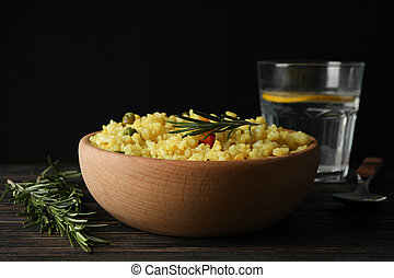 Composition with bowl of delicious rice on wooden table, close up