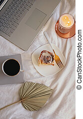 Lifestyle composition with cinnamon bun, coffee, burning candle and laptop on the bed.
