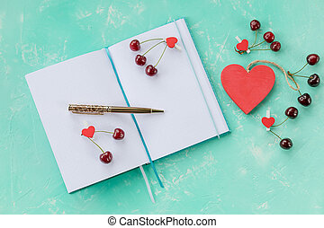 Vintage diary with handmade cover, cute small gift box wrapped with rough white paper and decorated with red jute, textile heart, dry herbal grass and piny cone on white wooden table.