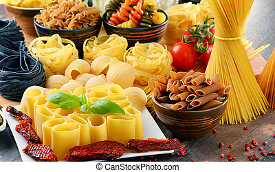 Composition with different sorts of pasta on kitchen table