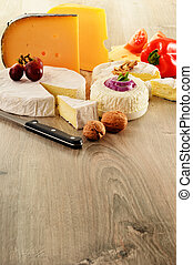 Composition with different sorts of cheese on wooden table