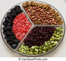 Composition with dried fruits and assorted nuts on a glass plate