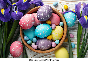 Composition with Easter eggs and Iris flowers on wooden background, top view