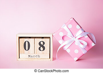 Composition with gift box and March 8 wood calendar on a pink background. Flat lay March 8