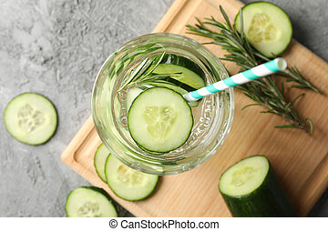 Composition with glass of cucumber water on grey background, top view