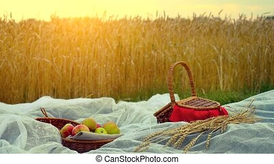 Composition with handmade wicker basket, apples and branch of wheat on cloth and placed in wheat field. 4k