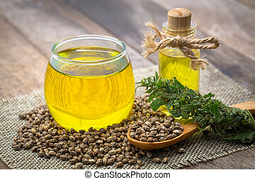 Composition with hemp oil and seeds on wooden background, CBD cannabis oil.