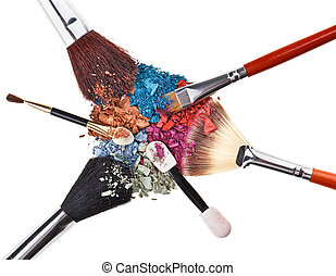 Composition with makeup brushes and broken multicolor eye shadows
