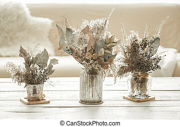 Composition with many dried flowers in vases .