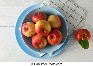 Composition with plate and apples on white wooden background, top view