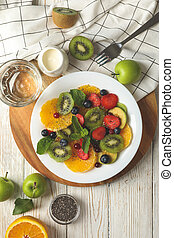 Composition with plate of fresh fruit salad on white wooden table, top view