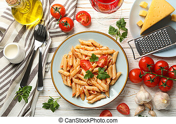 Composition with plate of tasty pasta and ingredients for cooking on wooden background